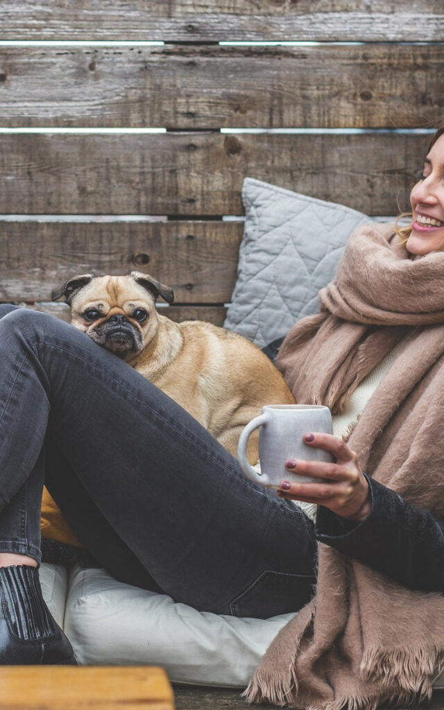woman with pink scarf and small dog on her lap holding a white mug