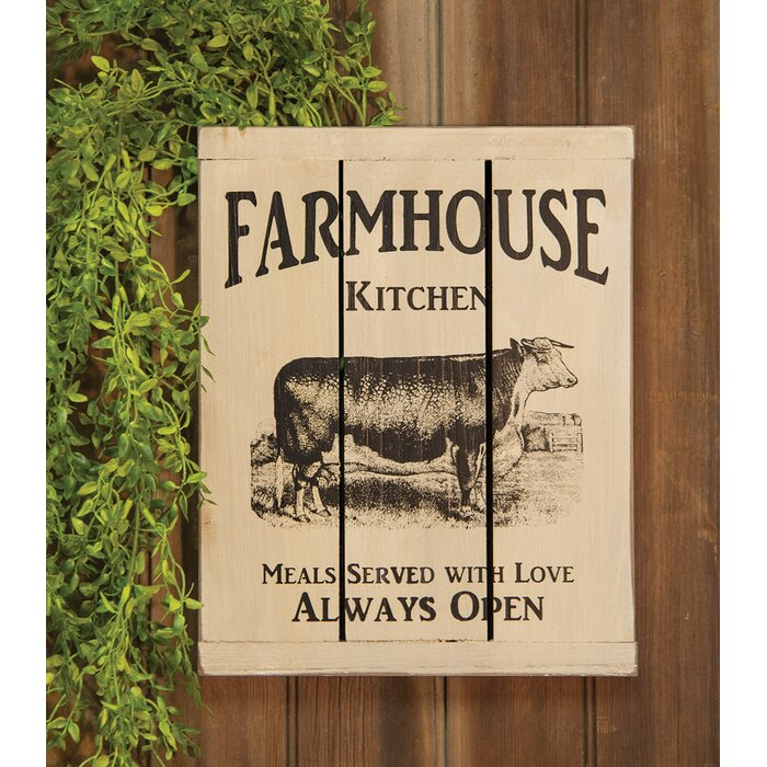 kitchen sign with image of cow, text says farmhouse kitchen, beige background, image and text are brown, hung on a wooden backdrop with plants