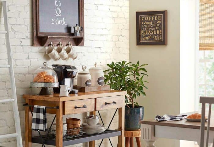 farmhouse style kitchen pantry with baker's rack, storage cannisters, plants and pictures on the wall