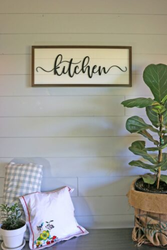 kitchen sign horizontal framed wall hanging with plant and pillows in the background