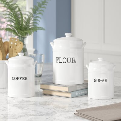 three white ceramic canisters for coffee, flour, sugar, on a marble countertop with plant and wooden spoons in background