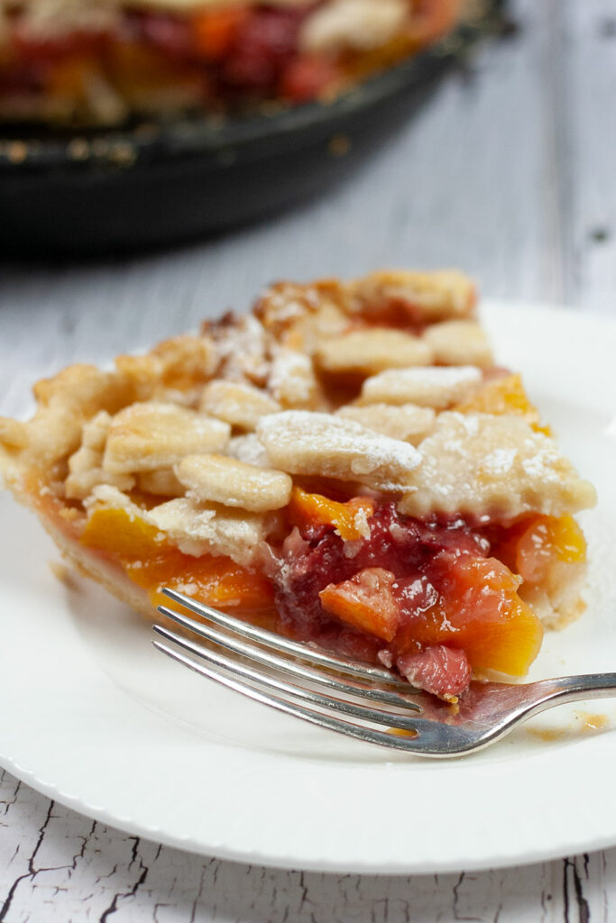slice of peach strawberry mango pie with fork and skillet in background