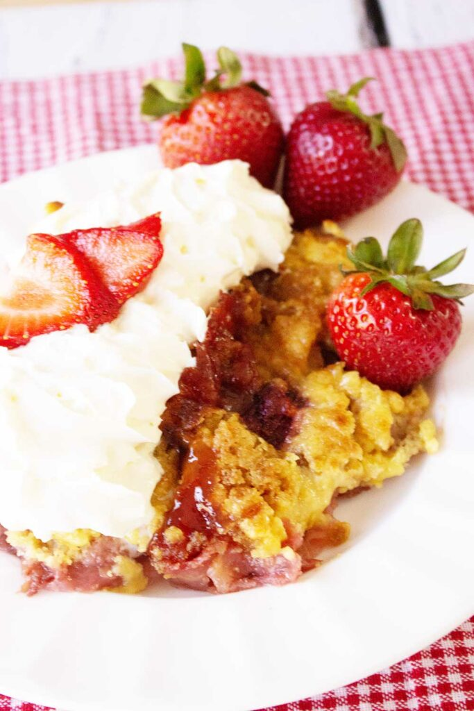 generous serving of strawberry rhubarb crumble with whipped cream and sliced strawberries on a white plate