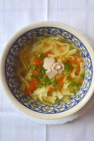 un bouillon dans un bol, les petites pâtes et une carotte coupée en dés