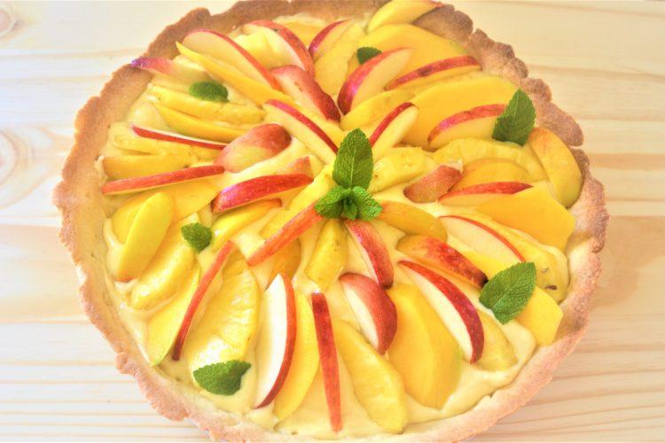 une tarte ronde, avec la creme, fruits jaunes, feuilles de menthe
