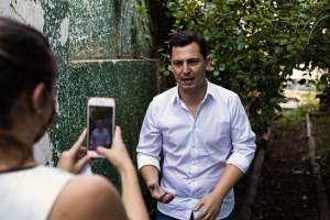 Pier está sendo filmado por um celular. Em primeiro um plano vemos os braços de um mulher segurando um celular que está apontado para ele. Ele está de pé e vestindo uma camisa branca. No fundo temos um muro verde e algumas arvores.