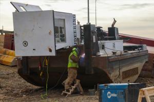 Crew member welding on the barge tug