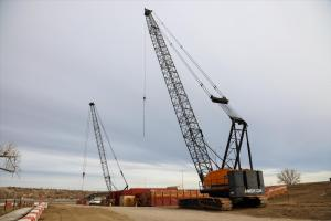 Worksite cranes moving barge platforms into position