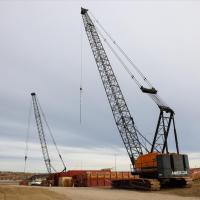 Worksite cranes moving barge platforms into position