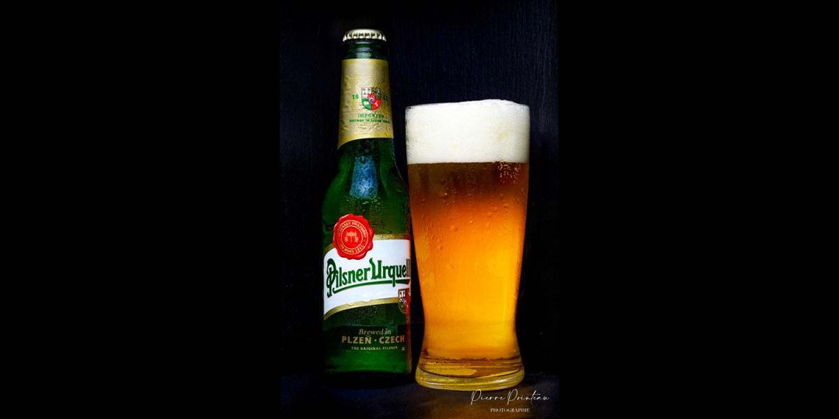 Photo packshot d'une bouteille et d'un verre rempli de Pilsner Urquell