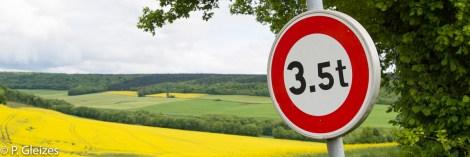 """Chemin rural sur l'ancienne frontiere de l'empire allemand, champ colza, paysage, panneau routier limitation 3,5 t -----------------  Après la défaite, l'accord de paix signé à Versailles le 26 février 1871 imposa l'annexion de l'Alsace-Moselle et une nouvelle frontière entre la France et l'Allemagne. Celle-ci courait du Luxembourg à la Suisse en bouleversant les pourtours des départements de la Moselle, de la Meurthe, des Vosges et du Haut-Rhin. En Lorraine, cette ancienne frontière perdure aujourd'hui, car le département actuel de la Meurthe-et-Moselle a conservé son exact tracé. L'entretien des routes départementales incombant aux Conseils Généraux, les goudrons de revêtement routier changent souvent de couleur quand l'on passe d'un département à l'autre. Deux guerres mondiales n'auront donc pas fait disparaitre ces lignes sur la chaussée. Plus de quatre mille bornes marquées d'un numéro et des lettres D et F ont été positionnées pour jalonner la nouvelle frontière de 1871. Aujourd'hui, certaines sont toujours visibles au bord des fossés. Les lettres D (Deutschland) ont presque toutes été martelées afin de les rendre illisibles. Entre 1871 et 1945, les Alsaciens-Mosellans ont changé cinq fois de nationalités. Cela explique que sur leurs monuments aux morts, à de rares exceptions, l'on n'y lit pas l'épitaphe """"Morts pour la France"""" mais plutôt """"A nos morts"""". Comment, en effet, commémorer le souvenir de ces hommes combattant pour l'armée allemande ?"""