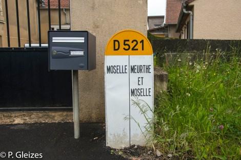 """Borne limite departementale, ancienne frontiere de l'empire allemand, boite aux lettres -----------------  Après la défaite, l'accord de paix signé à Versailles le 26 février 1871 imposa l'annexion de l'Alsace-Moselle et une nouvelle frontière entre la France et l'Allemagne. Celle-ci courait du Luxembourg à la Suisse en bouleversant les pourtours des départements de la Moselle, de la Meurthe, des Vosges et du Haut-Rhin. En Lorraine, cette ancienne frontière perdure aujourd'hui, car le département actuel de la Meurthe-et-Moselle a conservé son exact tracé. L'entretien des routes départementales incombant aux Conseils Généraux, les goudrons de revêtement routier changent souvent de couleur quand l'on passe d'un département à l'autre. Deux guerres mondiales n'auront donc pas fait disparaitre ces lignes sur la chaussée. Plus de quatre mille bornes marquées d'un numéro et des lettres D et F ont été positionnées pour jalonner la nouvelle frontière de 1871. Aujourd'hui, certaines sont toujours visibles au bord des fossés. Les lettres D (Deutschland) ont presque toutes été martelées afin de les rendre illisibles. Entre 1871 et 1945, les Alsaciens-Mosellans ont changé cinq fois de nationalités. Cela explique que sur leurs monuments aux morts, à de rares exceptions, l'on n'y lit pas l'épitaphe """"Morts pour la France"""" mais plutôt """"A nos morts"""". Comment, en effet, commémorer le souvenir de ces hommes combattant pour l'armée allemande ?"""