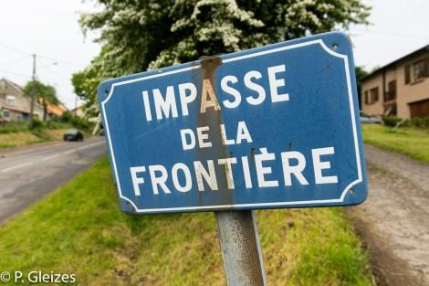 """Limite avec le Luxembourg. Plaque impasse de la frontiere, ancienne frontiere de l'empire allemand-----------------  Après la défaite, l'accord de paix signé à Versailles le 26 février 1871 imposa l'annexion de l'Alsace-Moselle et une nouvelle frontière entre la France et l'Allemagne. Celle-ci courait du Luxembourg à la Suisse en bouleversant les pourtours des départements de la Moselle, de la Meurthe, des Vosges et du Haut-Rhin. En Lorraine, cette ancienne frontière perdure aujourd'hui, car le département actuel de la Meurthe-et-Moselle a conservé son exact tracé. L'entretien des routes départementales incombant aux Conseils Généraux, les goudrons de revêtement routier changent souvent de couleur quand l'on passe d'un département à l'autre. Deux guerres mondiales n'auront donc pas fait disparaitre ces lignes sur la chaussée. Plus de quatre mille bornes marquées d'un numéro et des lettres D et F ont été positionnées pour jalonner la nouvelle frontière de 1871. Aujourd'hui, certaines sont toujours visibles au bord des fossés. Les lettres D (Deutschland) ont presque toutes été martelées afin de les rendre illisibles. Entre 1871 et 1945, les Alsaciens-Mosellans ont changé cinq fois de nationalités. Cela explique que sur leurs monuments aux morts, à de rares exceptions, l'on n'y lit pas l'épitaphe """"Morts pour la France"""" mais plutôt """"A nos morts"""". Comment, en effet, commémorer le souvenir de ces hommes combattant pour l'armée allemande ?"""