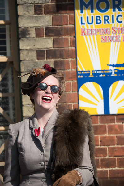 1940s weekend in Sheringham North Norfolk 2017. Smiling woman in fur stole in front of 1940s sign