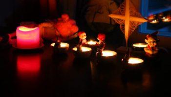 Nukke ihastelee kynttilöitä.