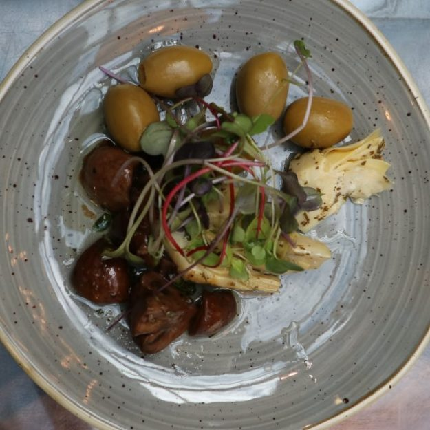 Alkuruokana nautin marinoituja luomuherkkusieniä, oliiveja ja latva-artisokkaa.
