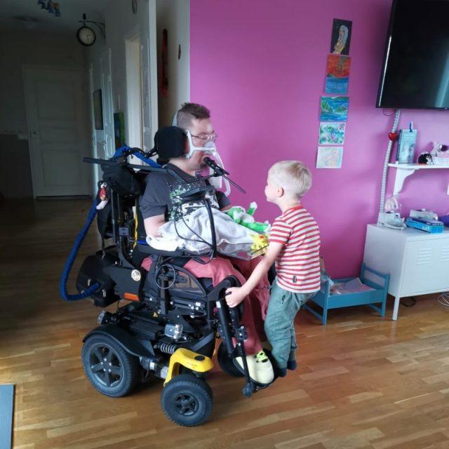 Heikki sähköpyörätuolin kyydissä.