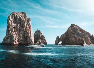 photo of boats on ocean near rock formations