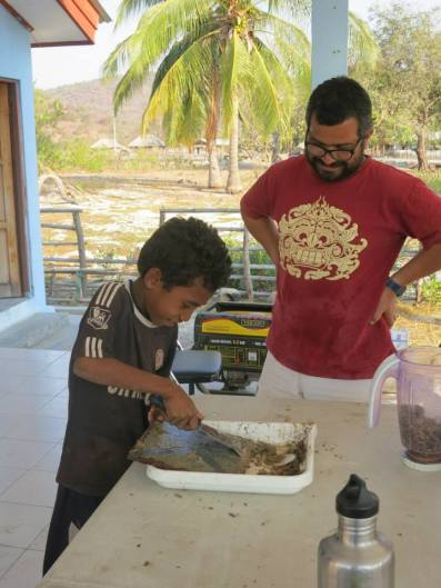 Rui Pinto works with a boy from Beacou to scrape plates from ARMS.