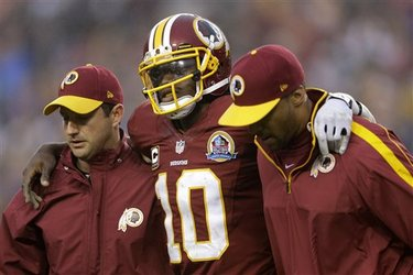 Redskins Quarterback Robert Griffin III is helped off the field (AP-Patrick Semansky)