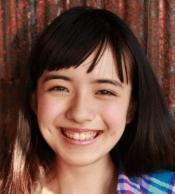 小島藤子がカラフルなチェックのシャツを着て笑顔でこっちを見ている画像