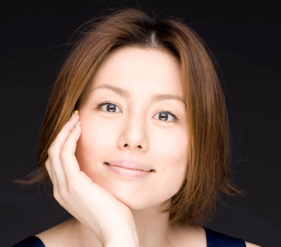 米倉涼子が頬杖をついて笑顔でこっちを向いている写真の画像