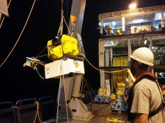 Deploying the ocean bottom seismometer (OBS) into the ocean. In the picture left to right: Ted Koczynksi and John Clapp.