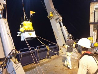 Deploying the ocean bottom seismometer (OBS) into the ocean. In the picture left to right: Carlos Bercerril and John Clapp.