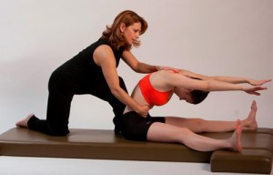 Pilates teacher instructing a client in a forward spine stretchnt