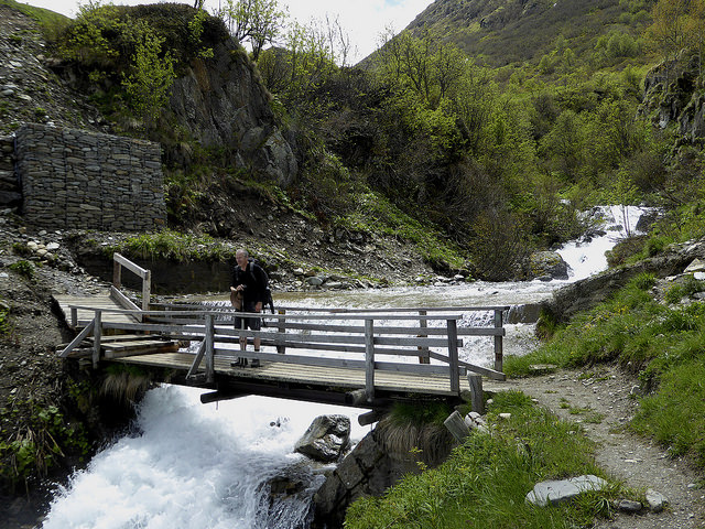 My walking companion Tim crossing a stream via a bridge in the high Alps