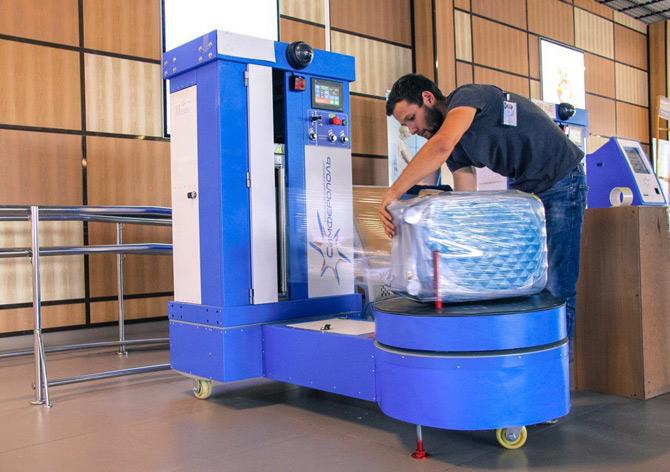 Упаковка багажа оператором камеры хранения
