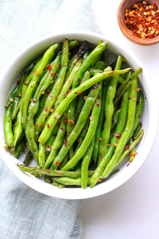 Super Easy Green Beans in a bowl topped with red pepper flakes