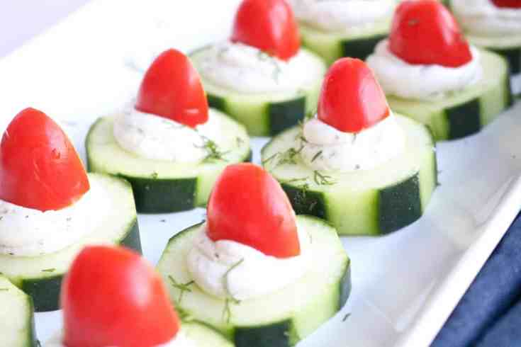 3 ingredient Cucumber Goat Cheese Bites - Crisp cucumber filled with creamy herb goat cheese topped with sweet cherry tomatoes. A fast healthy snack that even works great as an appetizer. Kid-Friendly and Vegetarian.