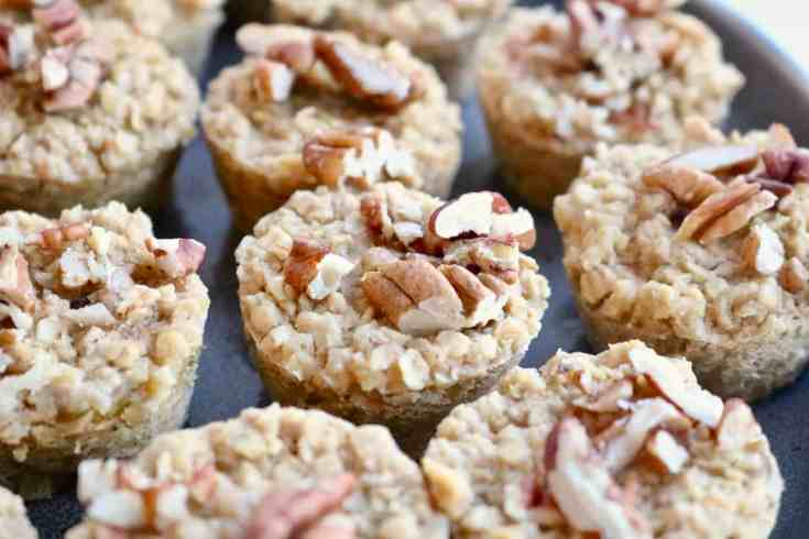 Mini oatmeal cups filled with oats, applesauce, peanut butter, apples, maple syrup and pecans.  These little packages of goodness are great for busy mornings or a healthy snack on the go! #easybreakfast, #simpleaotmeal, #veganrecipes