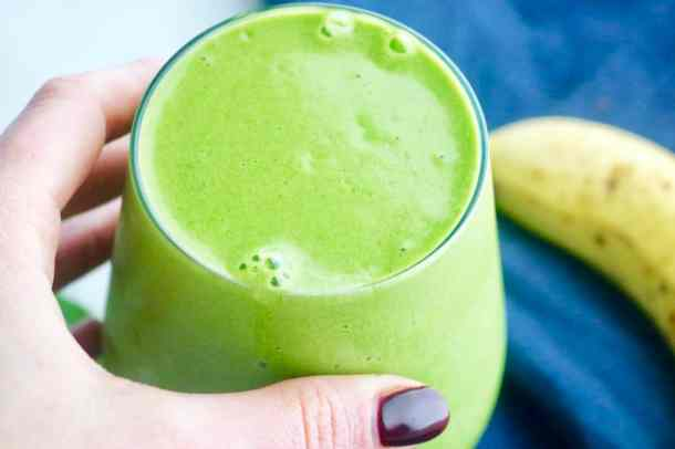 Hand holding glass of simple green smoothie