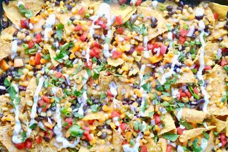 Crispy nachos covered with hearty black beans, roasted corn, fresh tomatoes, pepper, onion and melty cheese all topped with a drizzle of tangy greek yogurt and cilantro. Perfect game day recipe. Ready in 15 minutes! #gamedaynachos, #vegetariannachos, #easynachorecipe, #sheetpannachos, #blackbeanandcorn