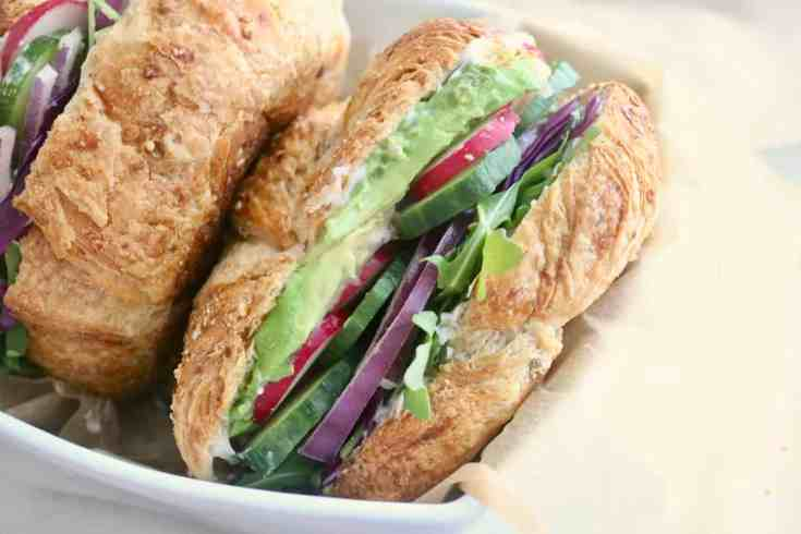 Crisp cucumbers, radishes, red onion and purple cabbage layered with creamy avocado, vegan mayo and peppery arugula all sandwiched between a buttery wholegrain croissant. The BEST Vegan Sandwich you need to try! Ready in 5 minutes! #vegansandwich, #veggiesandwich, #cucumber, #radishes, #avocado