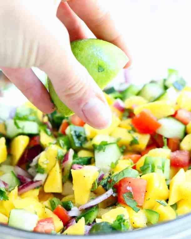 Squeezing lime juice onto mango salsa