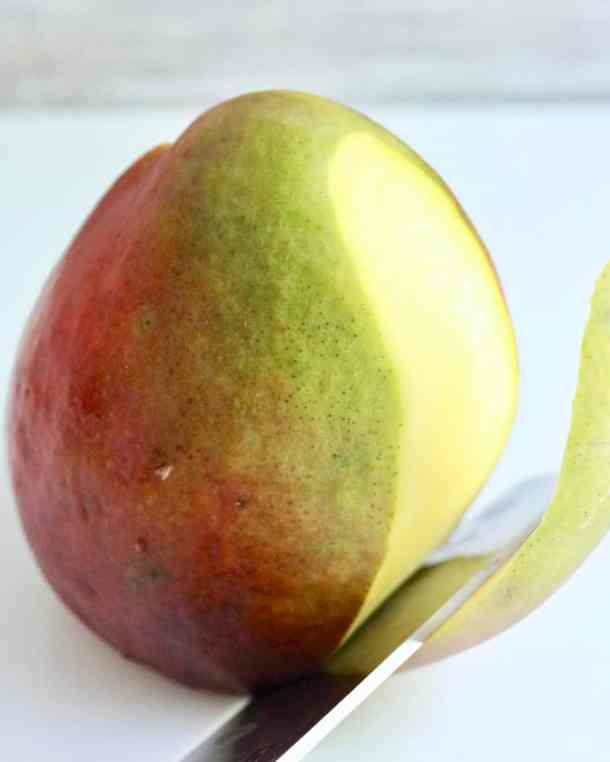 Knife sliceing skin off a mango