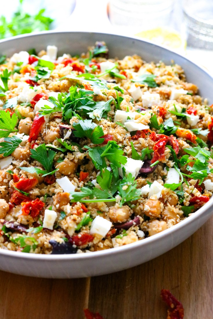 Easy Mediterranean Cauliflower Rice. Fluffy riced cauliflower, roasted in the oven and mixed with salty olives and feta cheese, sun-dried tomatoes, chickpeas, and fresh parsley. All generously drizzled with fresh lemon juice and olive oil. 20 minutes to make, gluten-free, low-carb, and delicious! #cauliflowerricerecipe #lowcarbrice #cauliflowerrecipes #easyhealthysides