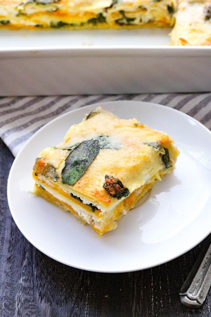 Hearty, roasted butternut squash nestled between layers of lasagna noodles, tender cooked spinach, and cheesy sauce. Less dairy than traditional lasagna but still all of that creamy goodness. One of the easiest recipes you will find for lasagna! #healthylasagnarecipes #butternutsquashlasagna #easylasaganrecipe #butternutsquash