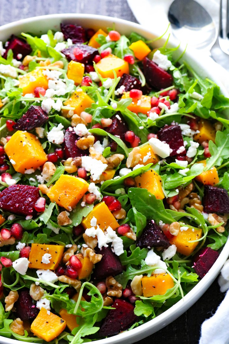 Spicy arugula, roasted butternut squash and beets mixed with crunchy walnuts, and creamy goat cheese. All drizzled with an incredible Orange Vinaigrette dressing! Simple lunch recipe, dinner salad or quick pick me up for those cold winter days. #roastedsquash #roastedbeets #winterarugulasalad #easyweeknightmeals #orangedressing