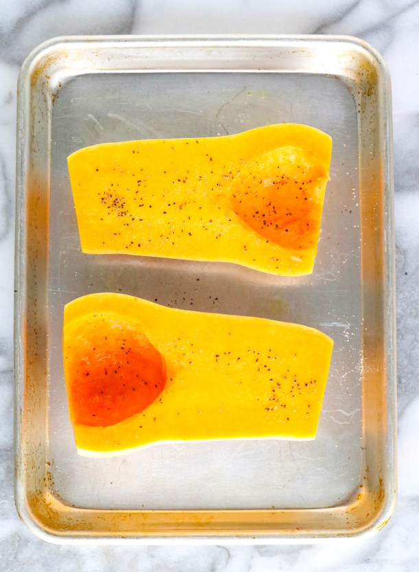 Halved butternut squash on a sheet pan topped with salt and pepper