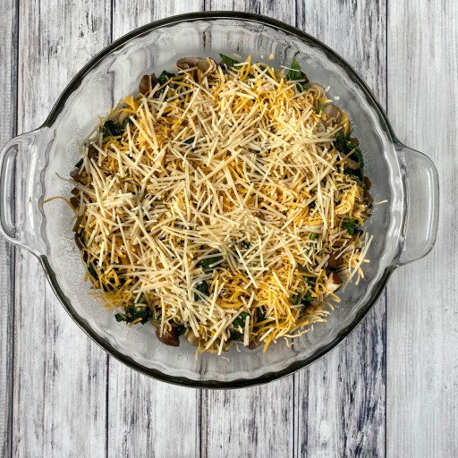 Cheese sprinkled on mushrooms and spinach