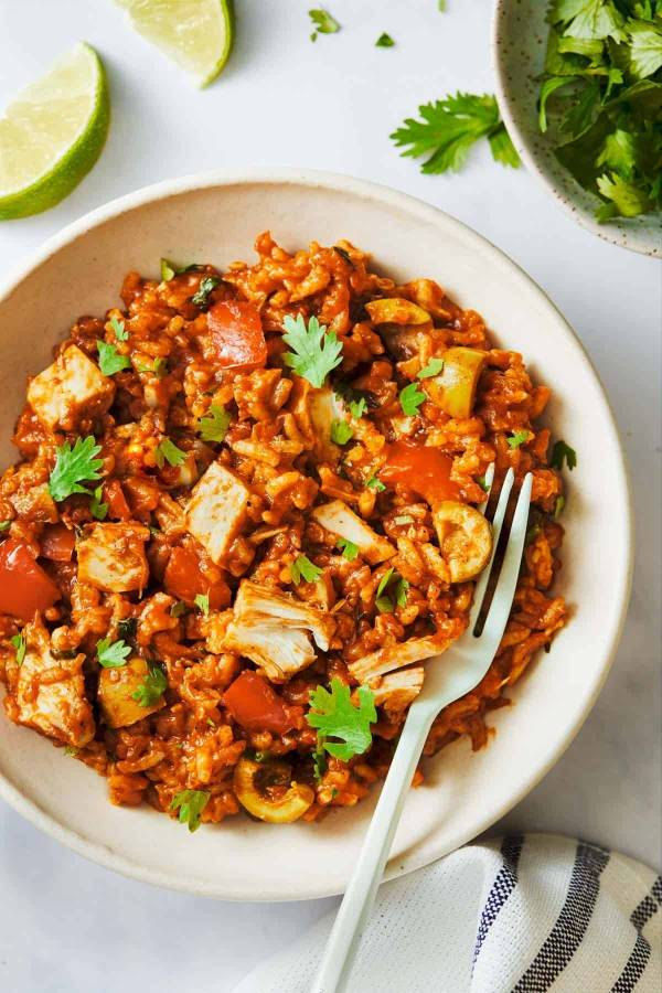 Arroz Con Pollo in a bowl with a fork.