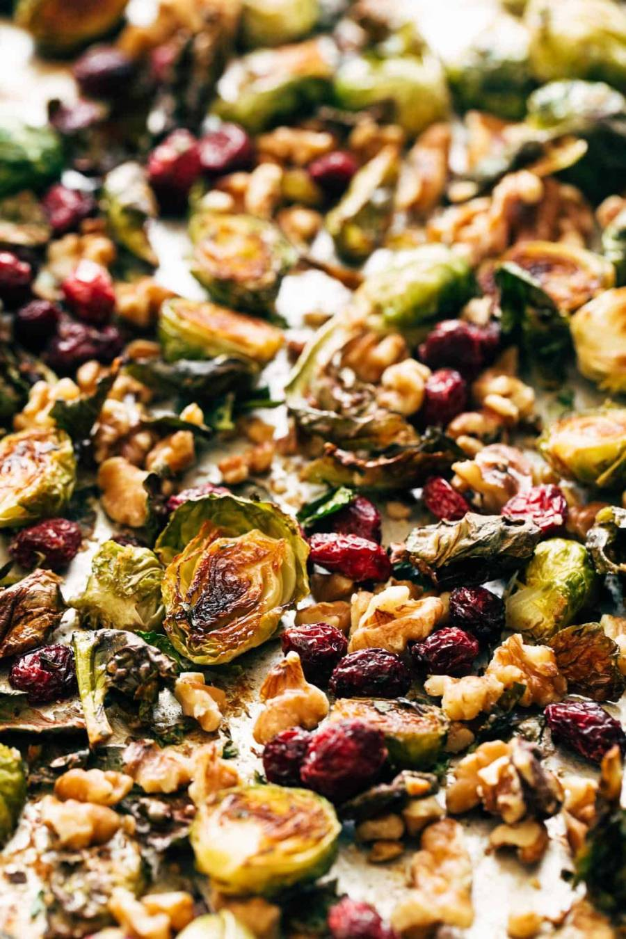 Close-up of roasted Brussels sprouts on a pan with walnuts and cranberries.