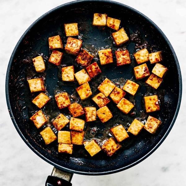 Sautèed tofu in a pan.