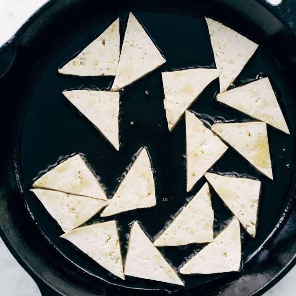 Tofu frying in a pan.