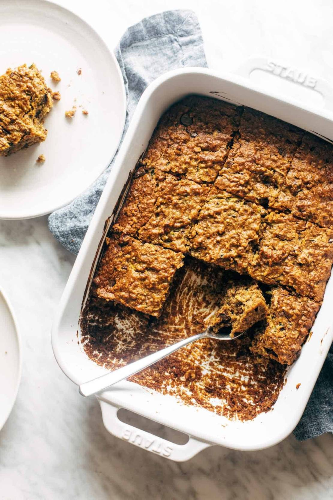 Overhead image of almond butter chocolate chip zucchini bars with a few bars taken out of the pan and a fork in the pan.