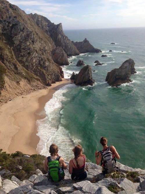 Isabella Limmer (links) und zwei Mädels der Wandergruppe blicken auf einen wunderschönen Strand: Den Praia Da Ursa.